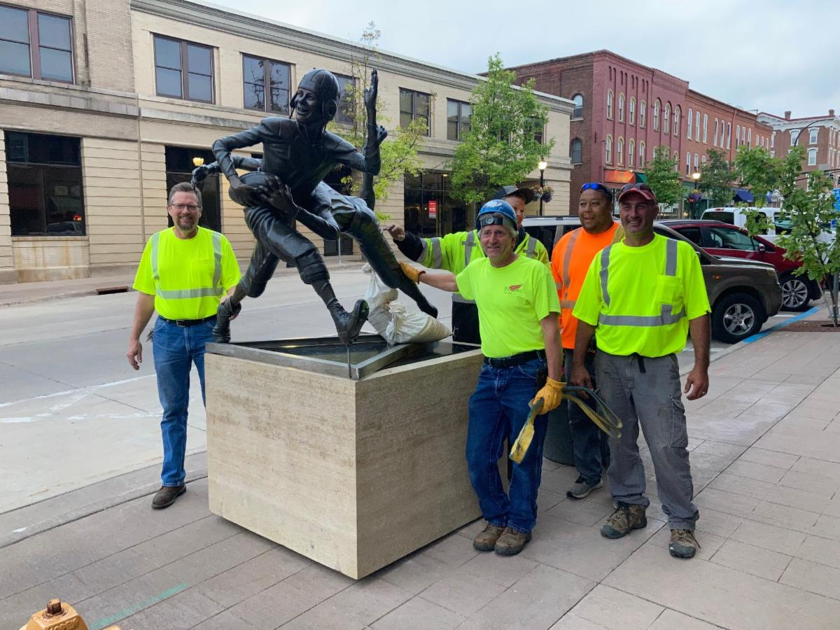 Photo of Public Works employees smiling next to a downtown art sculpture