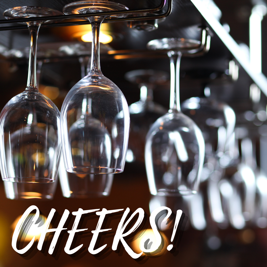 Image of empty glasses hanging upside down with Cheers in white letters along the bottom of the image