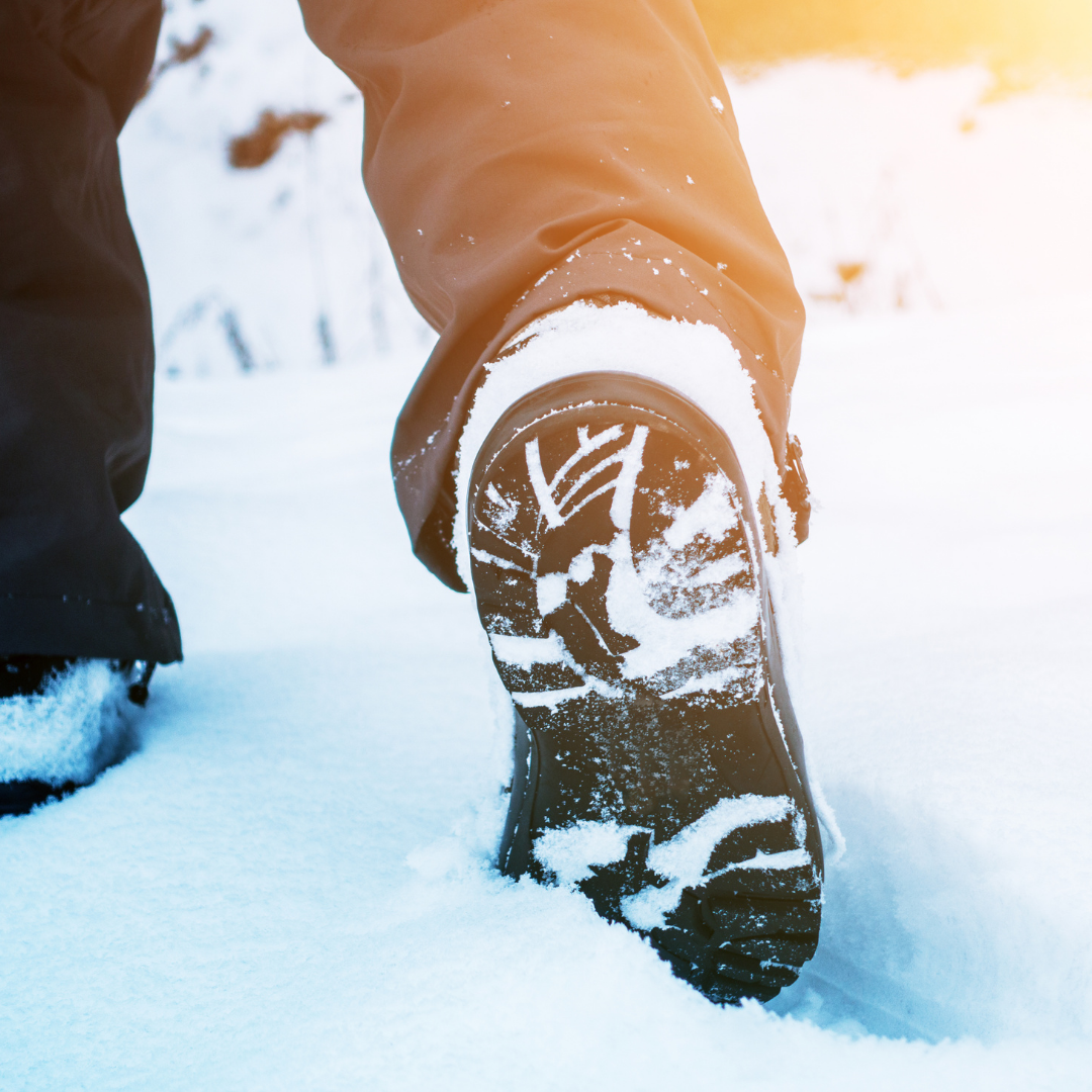 Photo of the sole of a winter boot as someone hikes through snow with sun flare in upper right corner