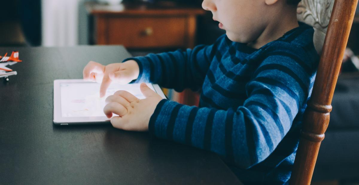 Photo of a child using a white tablet sitting at a table