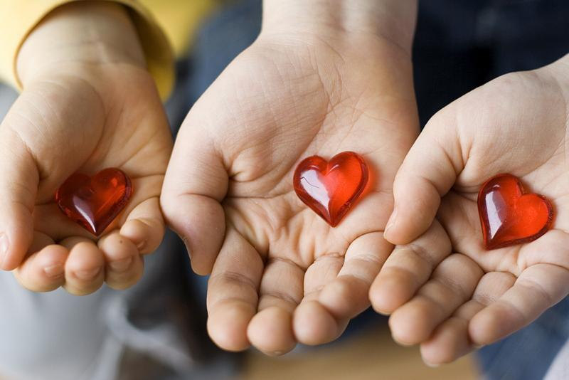 image of three hands each holding a plastic heart