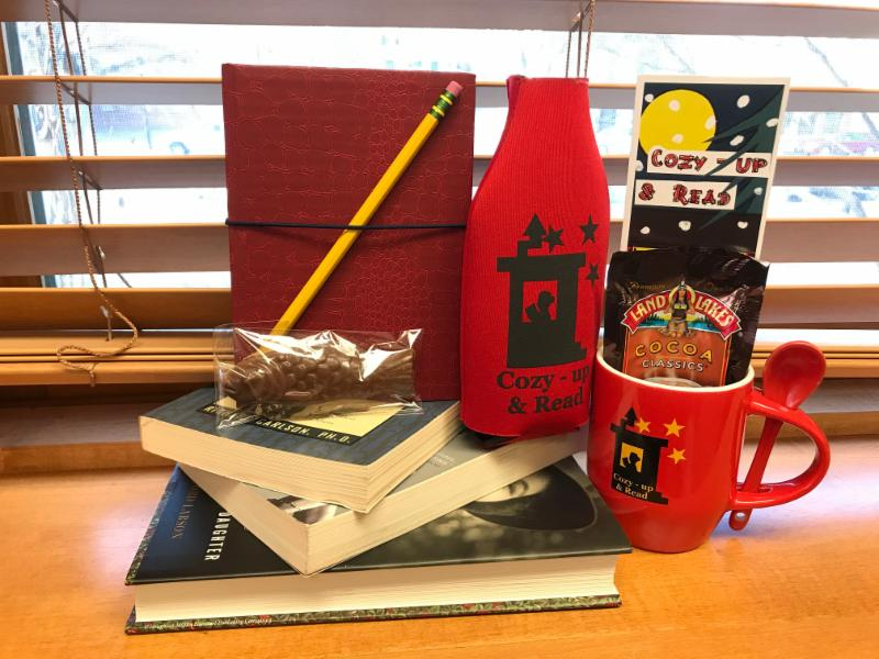 A photo of the Cozy Up and Read program gift bag stacked atop books on a windowsill.