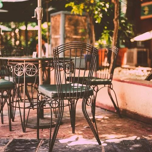 Image of wrought iron chairs around a table on a patio in summer