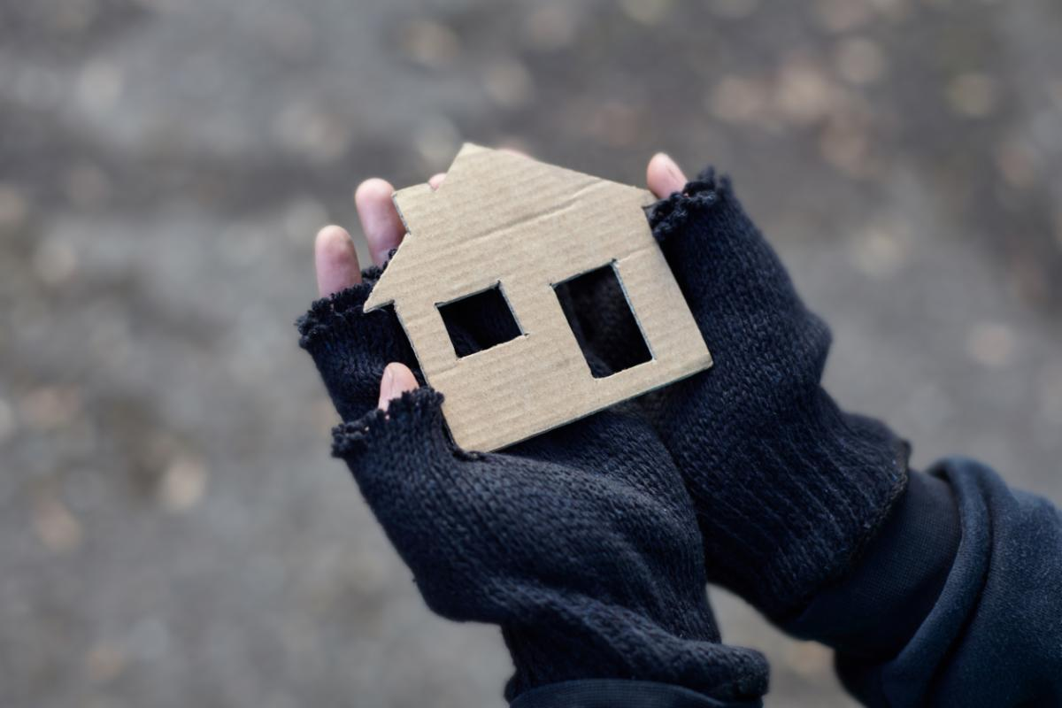 Image of a pair of hands in gloves holding a cardboard cut-out of a house