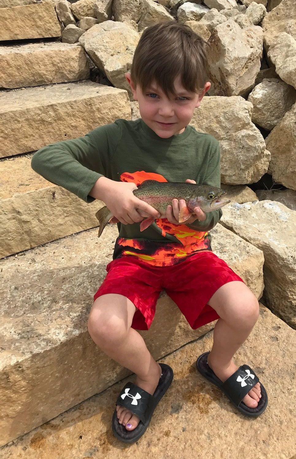 Young boy holding a rainbow trout he caught in Pottery Pond in Red Wing MN