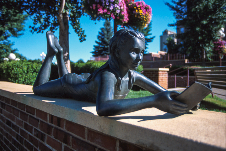 bronze statue of a girl lying on stomach reading a book