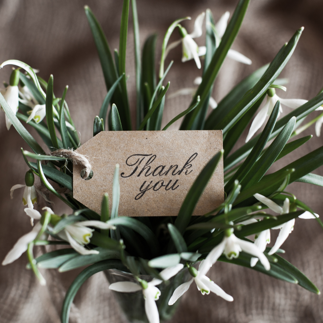 Aerial photo of flowers with a Thank You card in the middle