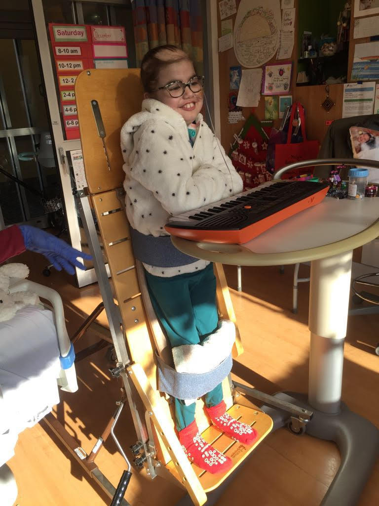 Picture of Isa standing at the keyboard and ready for music therapy.