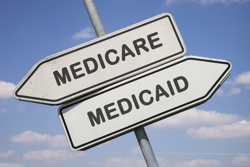 two white direction signs with arrows and the words medicare and medicaid_ political and social concept for us health care