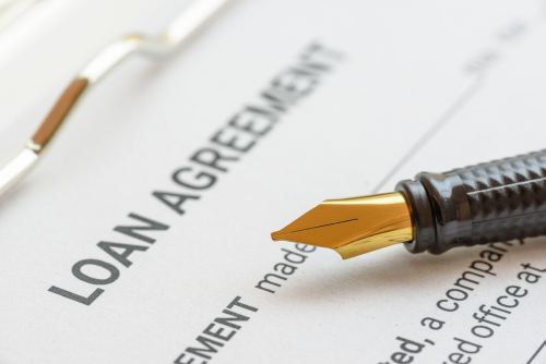 Business loan agreement or legal document concept   Fountain pen on a loan agreement paper form. Loan agreement is a contract between a borrower and a lender_ a compilation of various mutual promises.