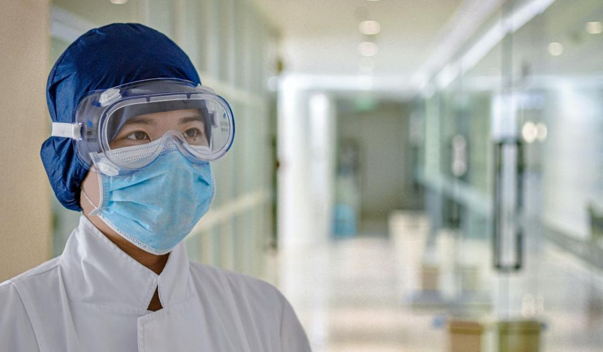Medical worker with face mask and eye protection