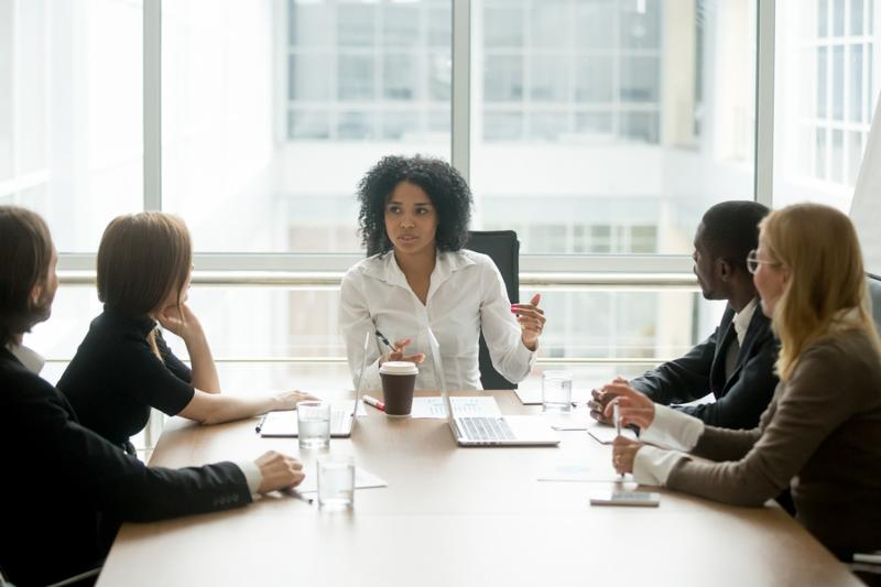 Black female boss leading corporate multiracial team meeting talking to diverse businesspeople_ african american woman executive discussing project plan at group multi-ethnic briefing in boardroom