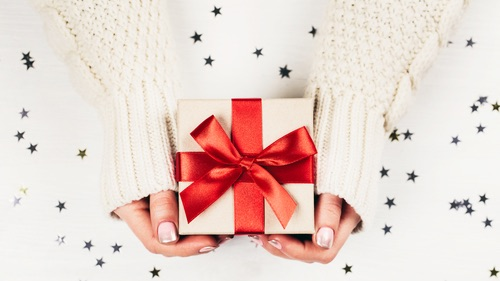Female hands holding present with red bow on white rustic sparkling background. Festive backdrop for holidays  Birthday_ Valentines day_ Christmas_ New Year. Flat lay
