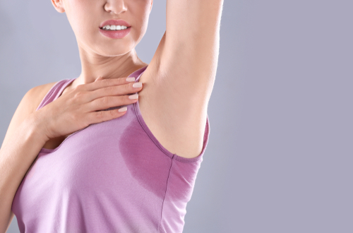 Young woman with sweat stain on her clothes against grey background_ space for text. Using deodorant