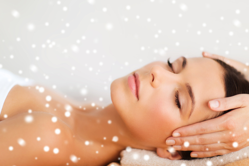 beauty_ health_ holidays_ people and spa concept - beautiful woman in spa salon getting face or head massage