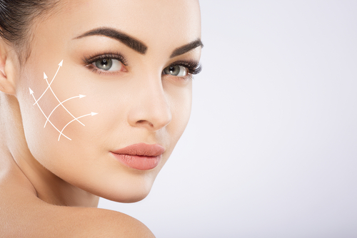Young girl with black hair fixed behind_ big eyes_ thick eyebrows and naked shoulders at gray background_ copy space_ beauty photo_ close up_ antiaging concept_ lifting arrows on face.