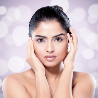 Beautiful Indian woman with healthy skin against blurred lights background. Asian beauty and skincare concept