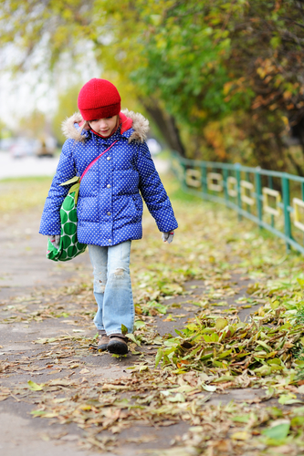 Funky little girl in blue coat walking down the street