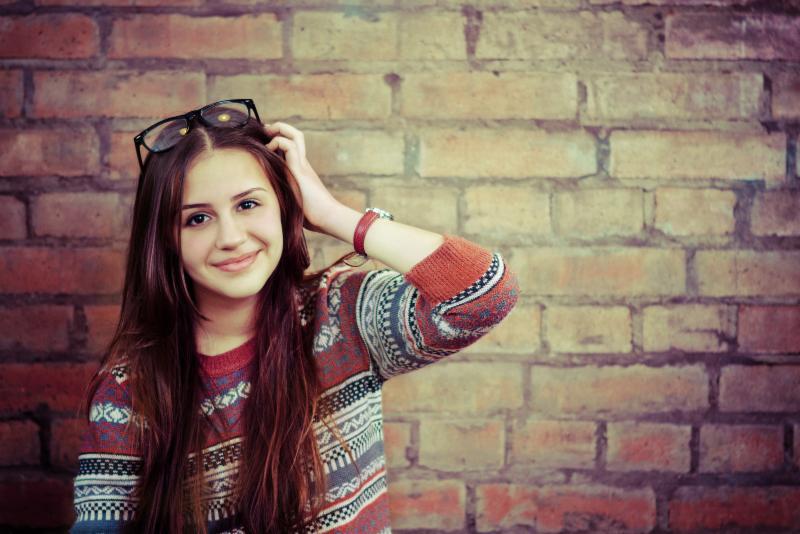 Hispanic teen girl against a brick wall