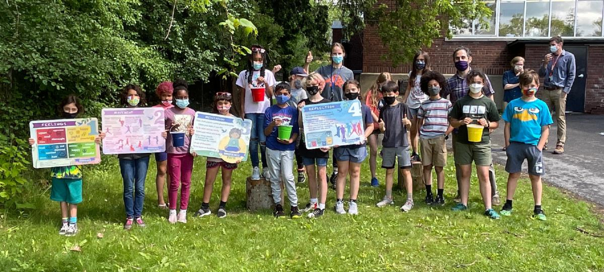 Group of students, each wearing protective face masks, and some holding up signs, stand near teachers at Belle Sherman Elementary as they unveil their mindfulness path.