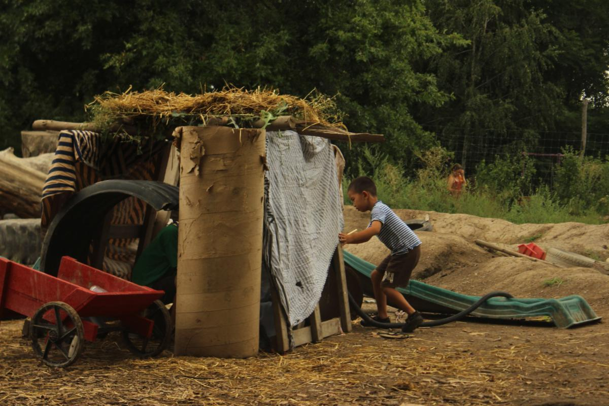 A child walks into a makeshift fort created with blankets, cardboard, and foliage.