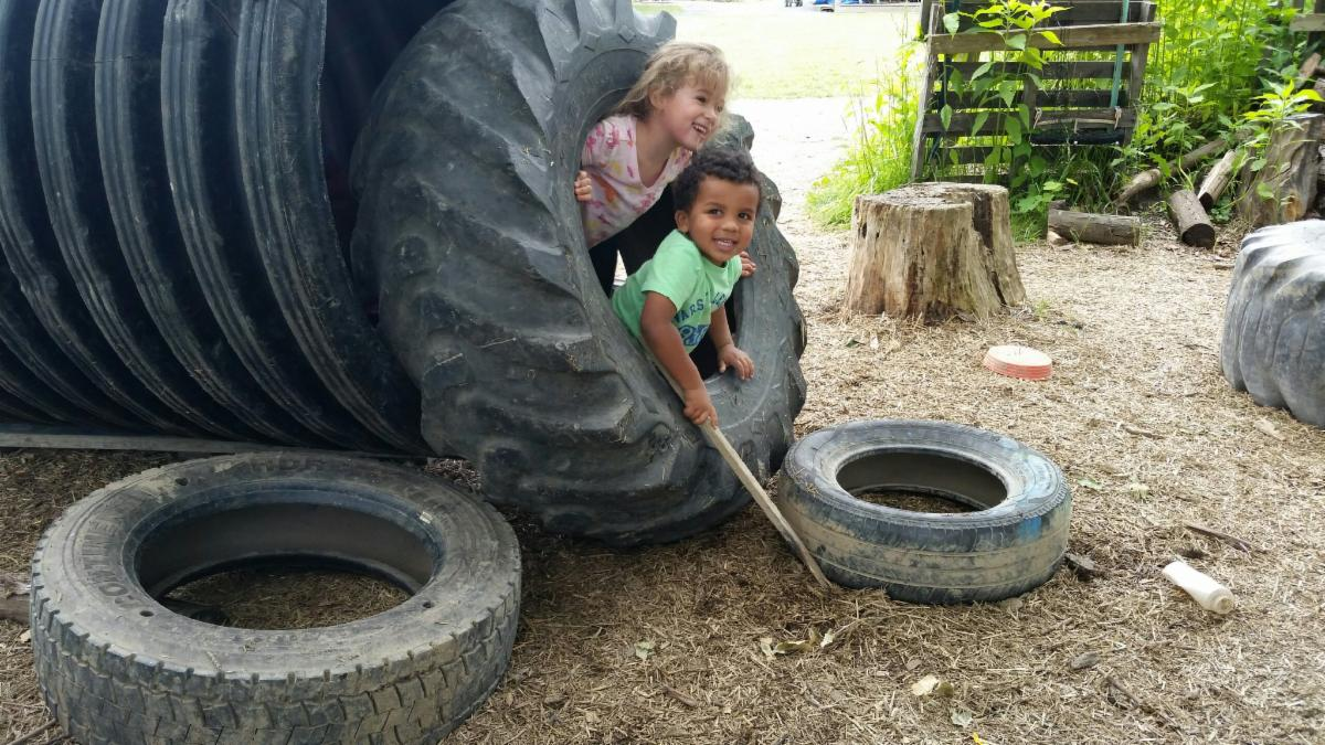 Two small children play in the HONAZ tube and large tires.