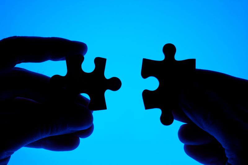 Hands joining puzzle pieces on blue background. Conceptual photo.