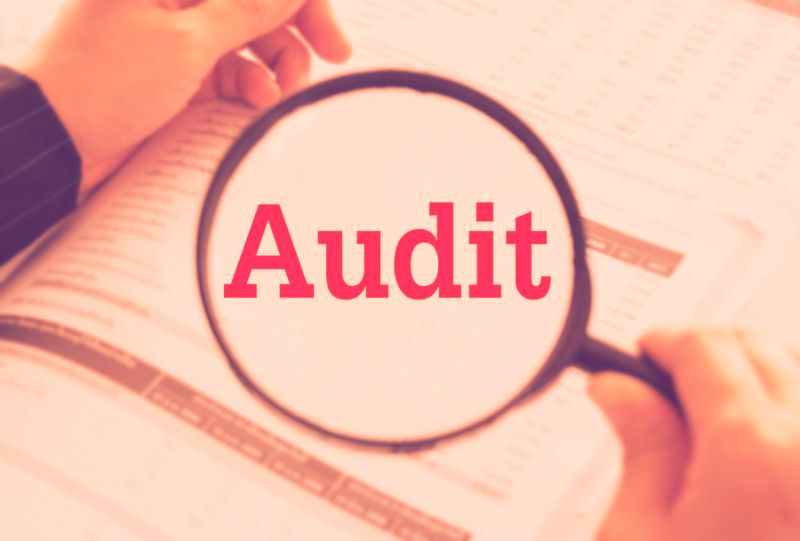 Audit concept. Auditor or IRS using magnifier auditing revenue in financial statement auditing tax process.
