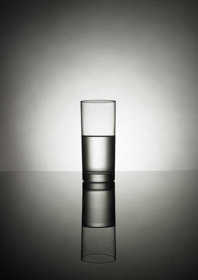 A half glass of water on a reflexion