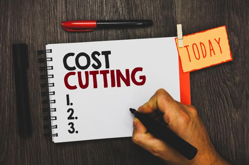 Text sign showing Cost Cutting. Conceptual photo Measures implemented to reduced expenses and improved profit Man holding marker notebook clothespin hold reminder cup markers wood table.