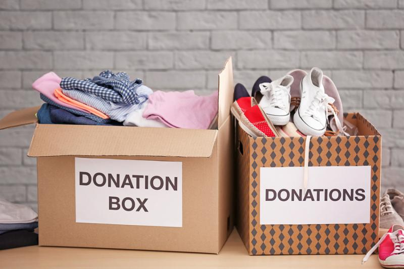 Donation boxes with clothes and shoes on table against brick wall