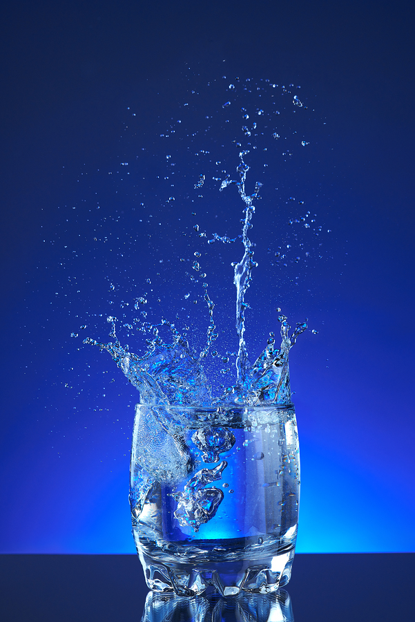 Water poured into a glass, splash, blue background, refreshing, freshness and health. Water bottle, water pitcher, blue liquid, ice, drops, motion, wave, splash, transparency blue liquid on water bottle or pitcher, ice, drops. Gradient background.