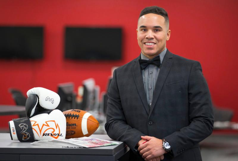 Nik Heftman in a suit and bowtie with a football and boxing gloves at the Iowa State Daily