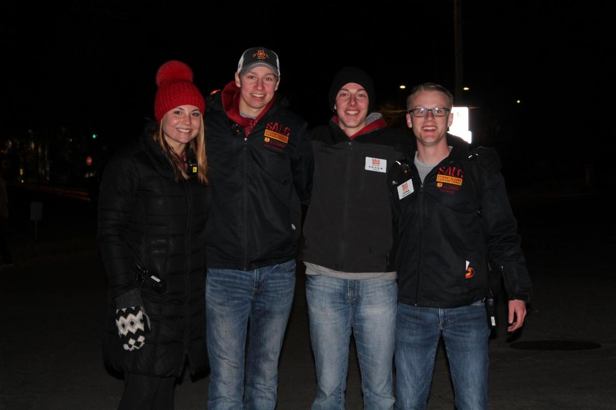 group of four people smiling at night