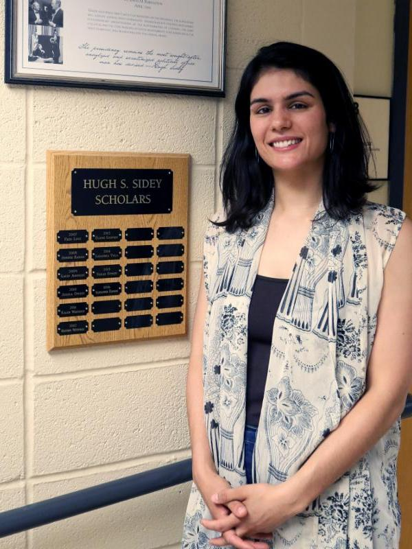female student with long dark hair standing next to Sidey Scholars plaque in Hamilton