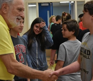 Paul Galan shaking hands with student