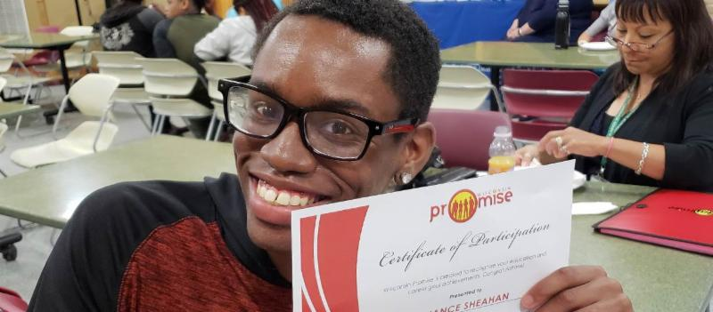 A Promise youth holding his certificate of participation