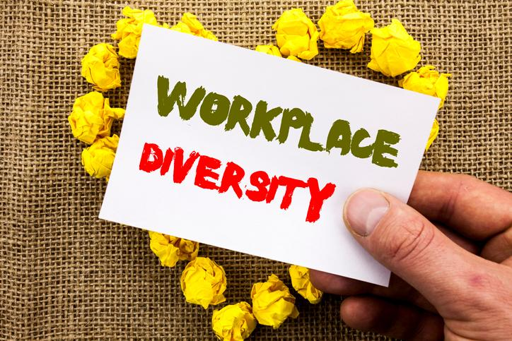 burlap background with yellow hart made out of paper balled up, hand holding card that says workplace diversity