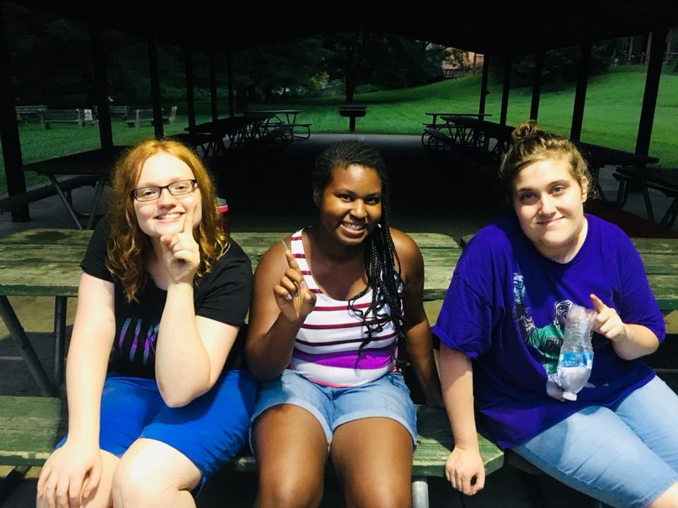 Three female Connect Program participants posing together for a picture outside at a Picnic Table.