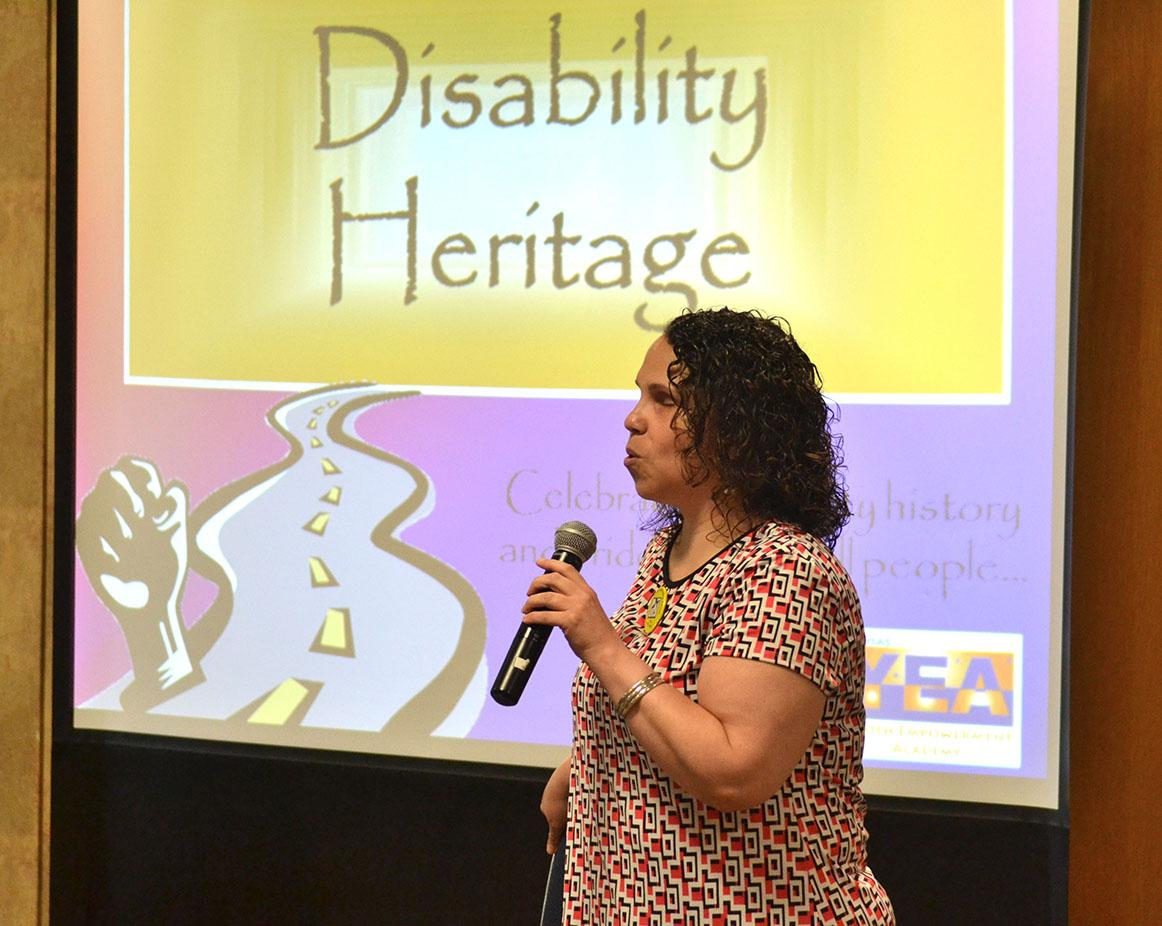 Julia holding a microphone speaking with a Disability Heritage powerpoint behind her
