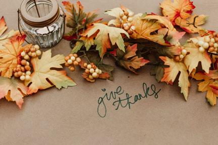 Multicolored leaves with the words Give Thanks in cursive below the leaves