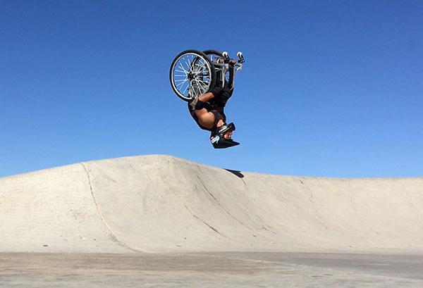 Aaron Fotheringham does a huge backflip in his wheelchair in a desert looking area