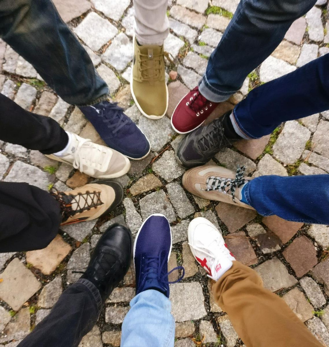 The feet of different people all pointing towards each other in a circle. The shoes and pants are all different colors.