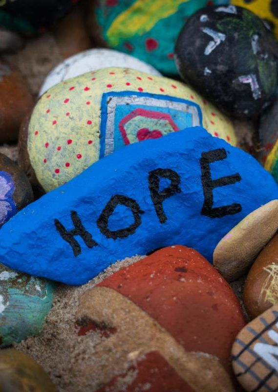 Multiple colored rocks with one rock that says hope