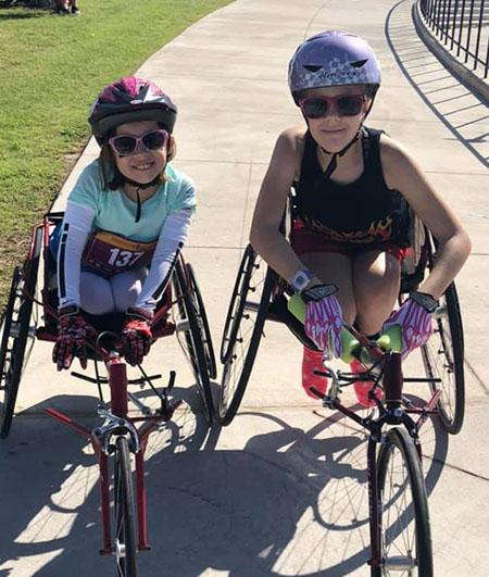 Isabel and a friend taking a picture in their hand cycles wearing glasses and helmets and smiling