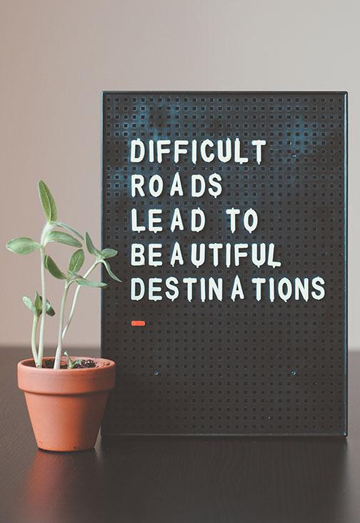 A sign saying Difficult Roads Lead to Beautiful Destinations with a plant next to it