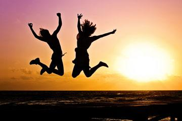 Two girls jump in the air in celebration as a beautiful sunset is behind them