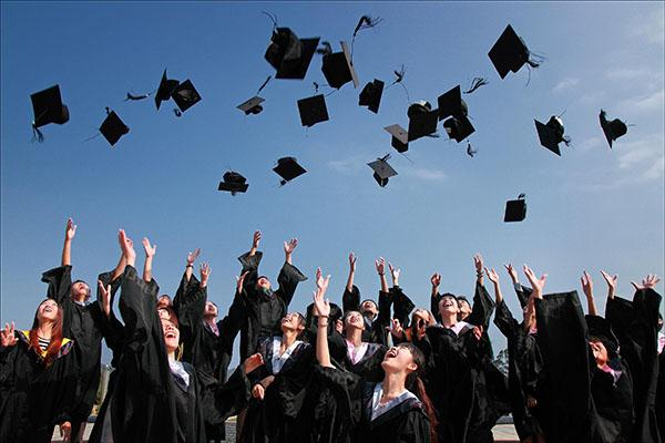 A large group of graduates throwing their caps in the air