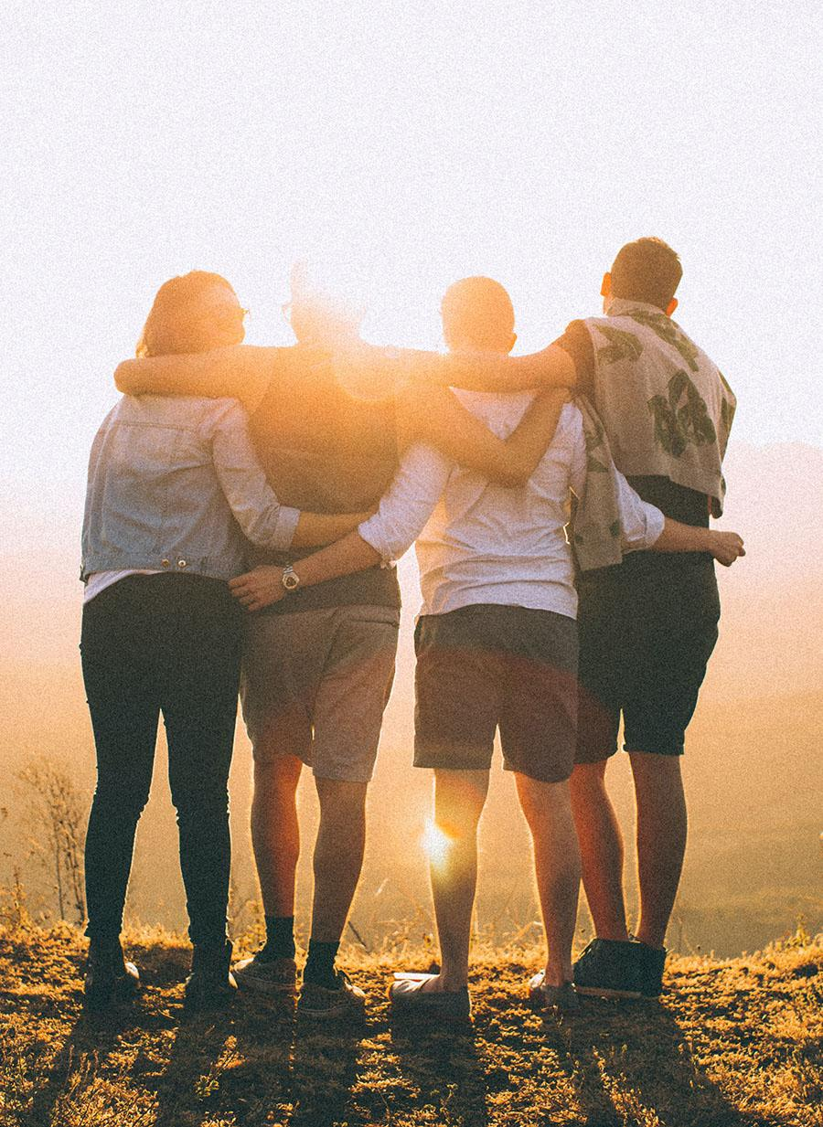 Four people with their arms around each other looking into a sunset