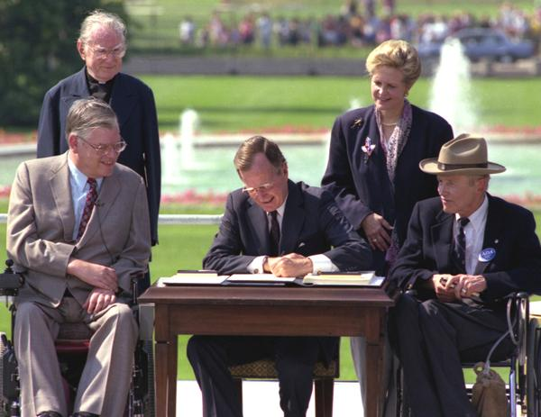 President signs ADA into law surrounded by leaders